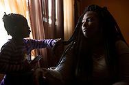 """CLIENT: THE INTERCEPT<br /> <br /> Kelly Holsey is comforted by her daughter Peyten Carter, 5, while looking at photos of her fiancé Keith Davis Jr. on her phone in the living room of her mother's home in the suburbs of Baltimore, Maryland. Holsey's fiancé Keith Davis Jr. was shot by police, who mistook him for a robbery suspect and fired 44 rounds. He survived but was arrested on murder charges stemming from what she is convinced was a planted gun. """"He is the second part of Freddie Gray. """"Freddie Gray passed away. Had he lived, he would have been arrested, had charges thrown on him, would have had to fight the court system, would have had to fight the State's Attorney's Office. And that's what Keith is going through now."""""""