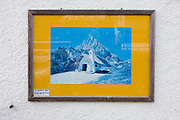 Detail of a framed picture of a Dolomites mountain hut, on sale in a  tourist shop selling tourist memorablia on Passo Falzarega (Pass) in south Tyrol, Italy.