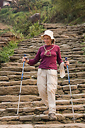 Trekker Liana Welty hikes down the long stone staircase that runs through the village of Chhomrong along the Annapurna Sanctuary Trek, Himalaya Mountains, Nepal.