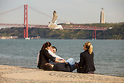 People enjoying Tagus riverside near to the Discoveries Monument in Lisbon with 25th of April bridge in the background. Located along the river were ships departed to explore and trade with India and Orient, the monument celebrates the Portuguese Age of Discovery (or Age of Exploration) during the 15th and 16th centuries and it was Inaugurated on 9 August 1960, its completion was one of several projects nationwide intended to mark the Comemorações Henriquinas (the celebrations marking the anniversary of the death of Henry the Navigator).