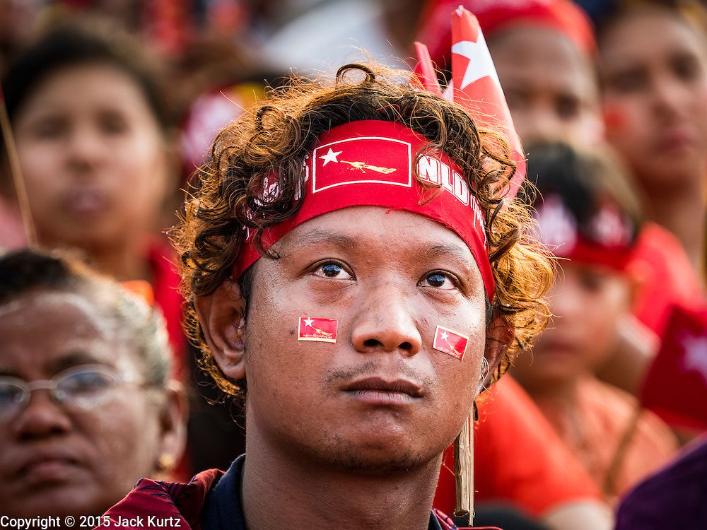 01 NOVEMBER 2015 - YANGON, MYANMAR:  Men listen to Aung San Suu Kyi at the NLD's last election rally of the 2015 election in the Yangon suburbs Sunday. Political parties are wrapping up their campaigns in Myanmar (Burma). National elections are scheduled for Sunday Nov. 8. The two principal parties are the National League for Democracy (NLD), the party of democracy icon and Nobel Peace Prize winner Aung San Suu Kyi, and the ruling Union Solidarity and Development Party (USDP), led by incumbent President Thein Sein. There are more than 30 parties campaigning for national and local offices.   PHOTO BY JACK KURTZ