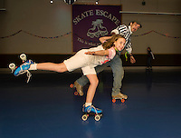 Skate guard Chuck Beckley gives Cassidy Dion a hand around the corner during Skate Escape's Skate a Thon to benefit the WLNH Children's Auction Friday evening.  (Karen Bobotas/for the Laconia Daily Sun)