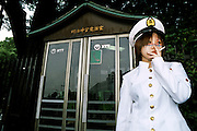A cos play girl in sailors uniform smoking a cigarette outside a public telephone box in Harajuku, Tokyo, Japan 2006