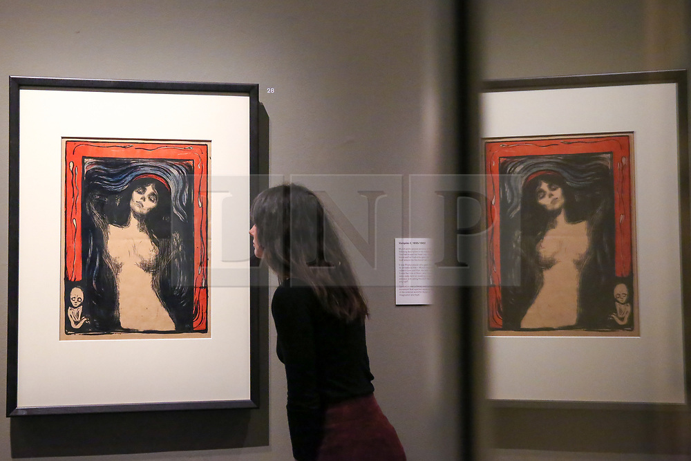 """© Licensed to London News Pictures. 08/04/2019. London, UK. A staff member views  Edvard Munch's """"Madonna, 1895/1902"""". Munch noted in an early description of this image that it shows """"Woman in a state of surrender - where she acquires the afflicted beauty of a Madonna"""". The explicit depiction of swimming sperm and a foetus on the border of the image provoked outrage at the time. Munch became disillusioned with the merits of free love, but remained convinced of the """"sanctity"""" of the creative act, suggested here by the red halo over the woman's head. <br /> <br /> The work of Norwegian artist Edvard Munch (1863-1944) - """"Edvard Munch: love and angst"""" at the British Museum opens from 11 April until 21 July 2019. The exhibition focus on Munch's remarkable and experimental prints – an art form which made his name and at which he excelled throughout his life – and will examine his unparalleled ability to depict raw human emotion. It will be the largest exhibition of Munch's prints in the UK for 45 years. Photo credit: Dinendra Haria/LNP"""