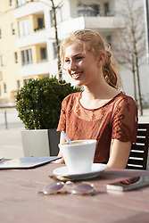 Young woman smiling at sidewalk cafe with digital tablet and coffee on table, Munich, Bavaria, Germany