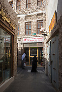 Doha, Qatar - January 31, 2017: An Arab man and woman walk trough the narrow, shop-filled lanes of Souq Waqif in Doha, Qatar