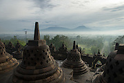 View between the Stupas of volcanoes Merapi and Merbabu shrouded in clouds, Borobudur, Kedu Valley, South Central Java, Java, Indonesia, Southeast Asia