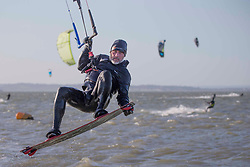 © Licensed to London News Pictures.27/03/2021. Southend-On-Sea,UK. A kite-surfer enjoys windy weather at the Thames Estuary in Southend-on-Sea, Essex. The weather forecasts predict sunny weather with strong winds in the southeast England.`Photo credit: Marcin Nowak/LNP