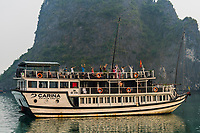 Passengers doing tai chi early in the morning aboard their tour ships, Halong Bay, North Vietnam. The bay features 3,000  limestone and dolomite karsts and islets in various shapes and sizes sprinkled over 1,500 square kilometers. It offers a wonderland of karst topography. It is a UNESCO World Heritage Site.