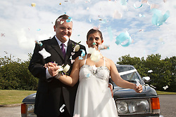 Bride who has cerebral palsy, with groom next to car at wedding ceremony with confetti.