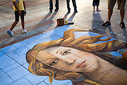 Pedestrians stop to admire artist Gabrielle Abbott's street painting of Botticelli's Venus on the Westlake Center Plaza in Seattle, Washington.