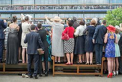 © Licensed to London News Pictures. 19/06/2014. Ascot, UK. People use vantage points to wave at Queen Elizabeth II as she enter the parade ring.  Day three, Ladies Day, at Royal Ascot 19th June 2014. Royal Ascot has established itself as a national institution and the centrepiece of the British social calendar as well as being a stage for the best racehorses in the world. Photo credit : Stephen Simpson/LNP