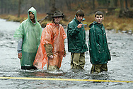 Liberty High School students stand in the middle of the Neversink River in Hasbrouck on Nov. 8, 2006. The students were at the river to test water quality. The second student from the right is checking the rive temperature.
