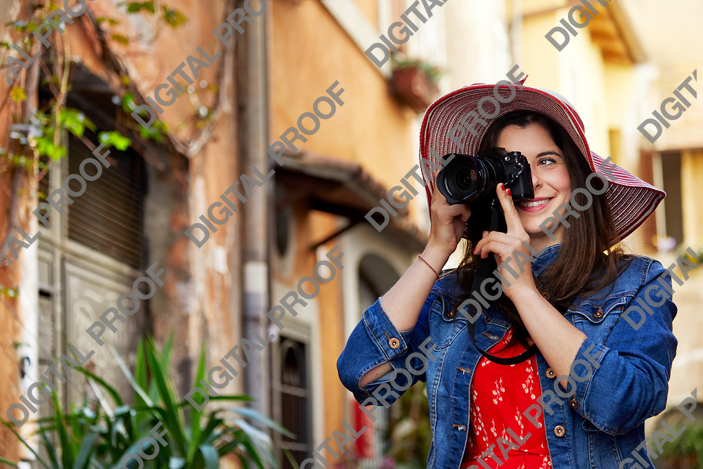 Cheerful young tourist woman in hat standing and taking shots with camera at Trastevere in Rome, Italy.