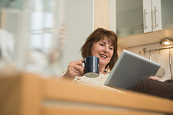Senior woman having a cup of tea and using a digital tablet in the kitchen, Munich, Bavaria, Germany