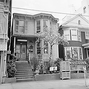 """Y-590319. Antique shop and tulip tree across the street from the Oregonian. 1329 SW Broadway between Columbia & Jefferson. Ladd Carriage House on the left, Rose Friend Apartments on the right. """"Psychic Reading"""" room (gypsy?) March 19, 1959"""