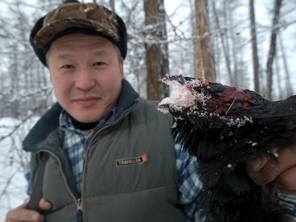 Jakutischer Jaeger mit einem geschossenen Vogel am fruehen Morgen in der sibirischen Taiga - ungefaehr 150 Kilometer entfernt von der sibirischen Stadt Jakutsk . Jakutsk hat 236.000 Einwohner (2005) und ist Hauptstadt der Teilrepublik Sacha (auch Jakutien genannt) im Foederationskreis Russisch-Fernost und liegt am Fluss Lena. Jakutsk ist im Winter eine der kaeltesten Grossstaedte weltweit mit bis zu durchschnittlichen Wintertemperaturen von -40.9 Grad Celsius.<br /> <br /> Yakutian hunter after shooting successfully a bird during an early morning hunt in the Siberian Taiga about 150 km from the city of Yakutsk. Yakutsk is a city in the Russian Far East, located about 4 degrees (450 km) below the Arctic Circle. It is the capital of the Sakha (Yakutia) Republic (formerly the Yakut Autonomous Soviet Socialist Republic), Russia and a major port on the Lena River. Yakutsk is one of the coldest cities on earth, with winter temperatures averaging -40.9 degrees Celsius.
