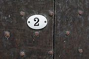 A detail of a number two and the rivets of an old wodden door in Ludlow, on 11th September 2018, in Ludlow, Shropshire, England UK.