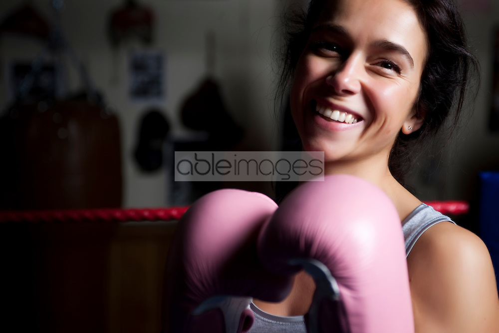 Close up of a woman wearing pink boxing gloves smiling