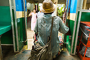 15 JUNE 2013 - YANGON, MYANMAR:   A man sits in the doorway of the Yangon Circular Train. The Yangon Circular Railway is the local commuter rail network that serves the Yangon metropolitan area. Operated by Myanmar Railways, the 45.9-kilometre (28.5mi) 39-station loop system connects satellite towns and suburban areas to the city. The railway has about 200 coaches, runs 20 times and sells 100,000 to 150,000 tickets daily. The loop, which takes about three hours to complete, is a popular for tourists to see a cross section of life in Yangon. The trains from 3:45 am to 10:15 pm daily. The cost of a ticket for a distance of 15 miles is ten kyats (~nine US cents), and that for over 15 miles is twenty kyats (~18 US cents). Foreigners pay 1 USD (Kyat not accepted), regardless of the length of the journey.     PHOTO BY JACK KURTZ
