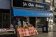 Part-time employee sells loaves and cakes outside Ye Olde Bakery in Herne Hill's Railton Road, south London.