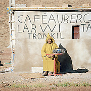A man sitting outside a café auberge with an old stereo near Ouarzazate, Morocco