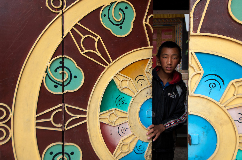 A Tibetan man peers out from a Tibetan Buddhist temple in Kathmandu.