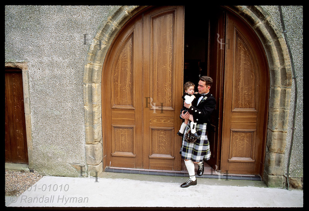Groomsman in kilt carries ringbearer, also in kilt, out church doors before wedding; Anstruther Scotland