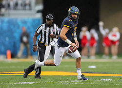 Sep 8, 2018; Morgantown, WV, USA; West Virginia Mountaineers quarterback Will Grier (7) rolls out of the pocket throw a pass during the first quarter against the Youngstown State Penguins at Mountaineer Field at Milan Puskar Stadium. Mandatory Credit: Ben Queen-USA TODAY Sports