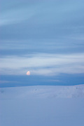 The moon at night above the Greenland ice cap during a British mountaineering expedition to Knud Rasmussens Land, East Greenland, Arctic, 2006.