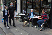 With the Coronavirus pandemic lockdown rules being eased, pubs and restaurant businesses are slowly re-opening and social distanced customers and their dog sit outside a cafe and people-watch on Wardour Street in Soho in the capitals West End, on 6th July 2020, in London, England.