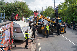 © Licensed to London News Pictures; 13/06/2020; Bristol, UK. New travellers facing eviction from the old gas works site on Glenfrome Road block the entrance with a caravan and occupy a contractor's JCB after bailiffs from GRC arrived on Saturday morning with police also in attendance who have closed off the road. The travellers have been living on the site, which is owned by Wales and West Utilities, for some weeks, and say that the eviction is illegal and is being done without any court papers. The travellers have been told that this is a common law eviction, but they say it is illegal because there is building on the land (hidden by foliage) which is permanently occupied and so the land is ancillary to the building and so a possession order must be granted by a court before an eviction can take place, and that no possession order has been granted. Photo credit: Simon Chapman/LNP.