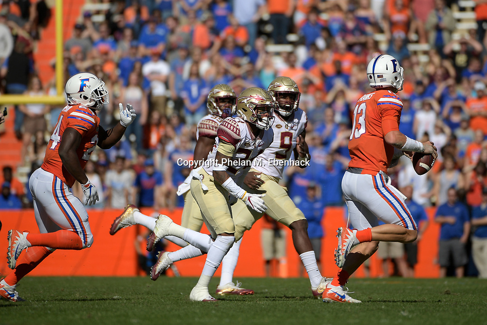 Florida State defensive back Cyrus Fagan (24) and defensive end Josh Sweat (9) pursue Florida quarterback Feleipe Franks (13) during the first half of an NCAA college football game Saturday, Nov. 25, 2017, in Gainesville, Fla. (Photo by Phelan M. Ebenhack)