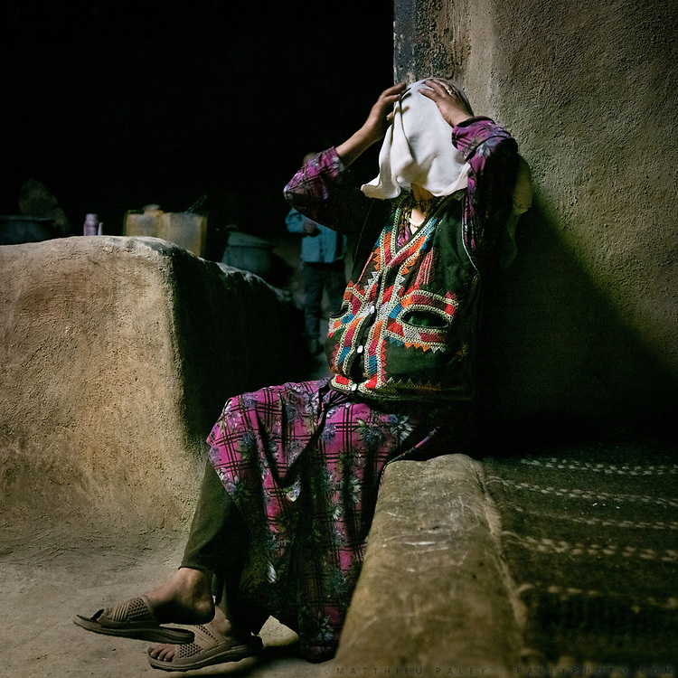 Woman readjusting her veil. House of Arif Baig.<br /> The traditional life of the Wakhi people, in the Wakhan corridor, amongst the Pamir mountains.