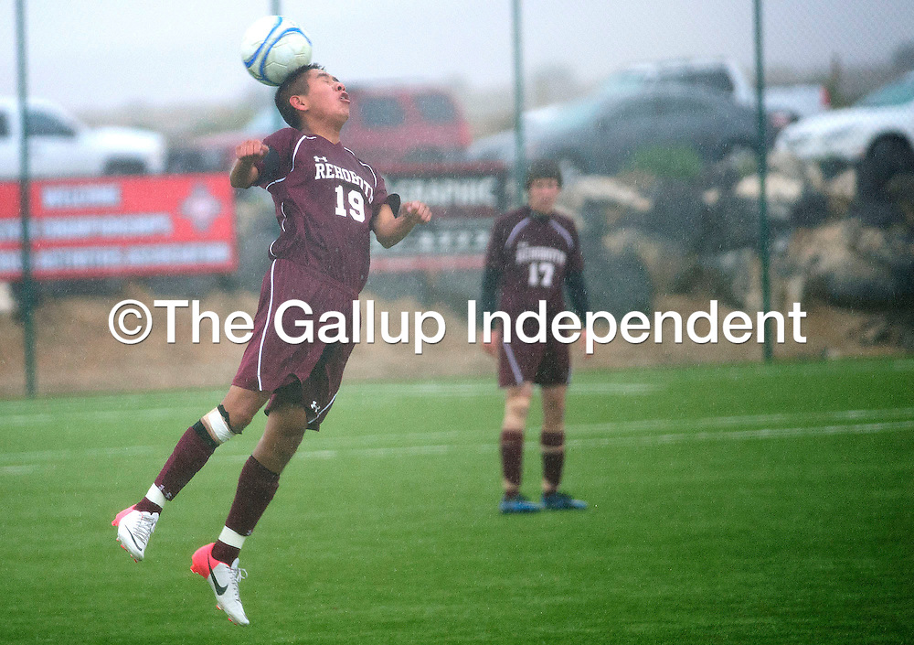 110912  Adron Gardner<br /> <br /> Rehoboth Lynx Tyler Begay (19) gets a header under sheets of rain while playing the Sandia Prep Sundevils in the state tournament at Volcano Vista High School in Albuquerque Friday.