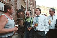 24 AUG 2000, NAUMBURG/GERMANY:<br /> Gerhard Schroeder, SPD, Bundeskanzler, trinkt ein Bier, mit einem Hufschmied, einen Kutscher, und dessen frisch beschlagenen Kaltblutpferd, auf einem Gehoeft in der Naehe von Naumburg, Sommerreise des Kanzlers durch die Ostdeutschen Bundeslaender<br /> IMAGE: 20000824-01/03-31<br /> KEYWORDS: Gerhard Schröder, Pferd, Tier, horse, animal, Hufeisen, Handwerk, Arbeit, work, beer, Alkohol, alcohol, Getraenk, drink