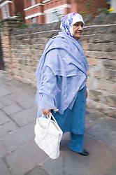 Older woman walking along a road carrying a  bag