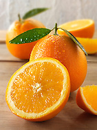 Fresh oranges whole and cut halves with leaves