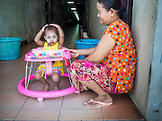 """11 JUNE 2015 - MAHACHAI, SAMUT SAKHON, THAILAND:  A Burmese migrant and her child in the hallway of a tenement building for migrant workers in Mahachai. Labor activists say there are about 200,000 migrant workers from Myanmar (Burma) employed in the fishing and seafood industry in Mahachai, a fishing port about an hour southwest of Bangkok. Since 2014, Thailand has been a Tier 3 country on the US Department of State Trafficking in Persons Report (TIPS). Tier 3 is the worst ranking, being a Tier 3 country on the list can lead to sanctions. Tier 3 countries are """"Countries whose governments do not fully comply with the minimum standards and are not making significant efforts to do so."""" After being placed on the Tier 3 list, the Thai government cracked down on human trafficking and has taken steps to improve its ranking on the list. The 2015 TIPS report should be released in about two weeks. Thailand is hoping that its efforts will get it removed from Tier 3 status and promoted to Tier 2 status.       PHOTO BY JACK KURTZ"""