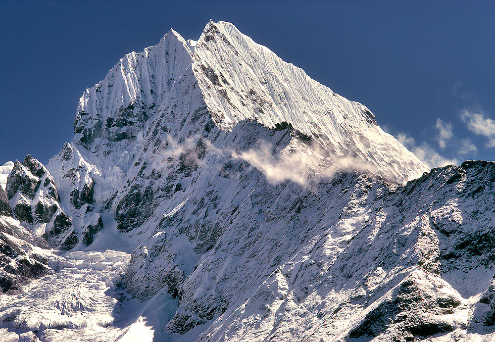 The jagged peaks of Tamserku, at 21,680 ft., jut into the blue skies of the Khumbu Himalaya in Sagarmatha National Park in Nepal.