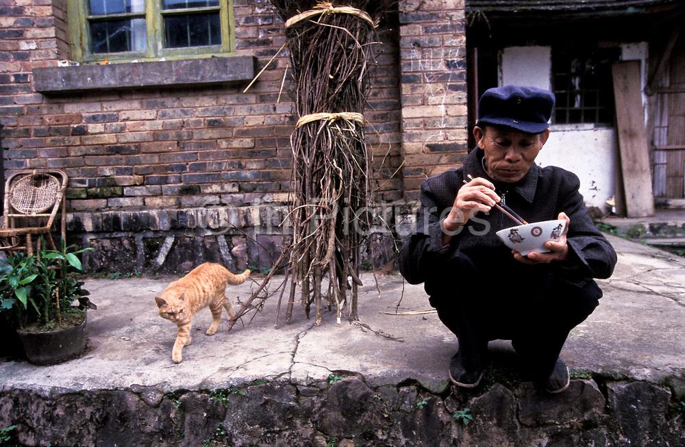 Chen Yi He, Chinese Herbalist, having breakfast at home, Xiao Meng Yang town, Xishuangbanna, China