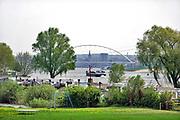 Nederland, Slijk Ewijk, 23-4-2019Een binnenvaartschip vaart over de Waal richting Nijmegen en Duitsland . Het passeert juist  de camping de Grote Altena die aan de Waal ligt . De nieuwe Waalbrug, stadsbrug, de Oversteek is te zien evenals de stad met  de stevenskerk .Foto: Flip Franssen