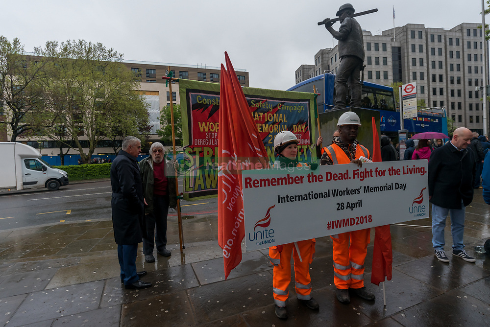 April 28, 2018 - London, UK. 28th April 2018. Unite workers pose with a large poster 'Remember the Dead. Fight for the Living' at the start of the International Workers' Memorial Day rally at the statue of a building worker on Tower Hill remembering all those killed at work, around 500 in the last ten years, mainly in the construction industry, as well as those injured, disabled and made unwell, almost all in preventable incidents. The actual number of work-related deaths is several orders of magnitude greater, estimated at over 150 per day, but the official figures only include those actually killed at work for which accident reports have been submitted - and not for example the 18,000 that die years after exposure from work-related cancers. The Government 'red tape initiative' has resulted in fewer and less rigorous safety inspections and the removal of many important safety checks that protect workers. At the centre of the event was a coffin with a pair of empty boots and a hard hat, and after the speeches by Peter Kavanagh, secretary London & Eastern Region Unite, Helen Clifford, a solicitor working on workplace deaths, Moyra Samuels of Justice4Grenfell and Gail Cartmel, Assistant General Secretary Unite, wreaths were laid and there was a period of silence before black balloons were released, one for each worker killed this year in the construction industry. Peter Marshall/Images Live (Credit Image: © Peter Marshall/IMAGESLIVE via ZUMA Wire)