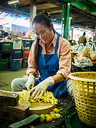 "19 DECEMBER 2013 - BANGKOK, THAILAND:    A vendor slices ginger in the flower market. Pak Khlong Talat (""the market at the mouth of the canal"") is a market in Bangkok that sells flowers, fruits, and vegetables. It is the primary flower market in Bangkok. It is located on Chak Phet Road and adjacent side-streets, close to Memorial Bridge. The market is open 24 hours, but is busiest before dawn, when boats and trucks arrive with flowers from nearby provinces.       PHOTO BY JACK KURTZ"