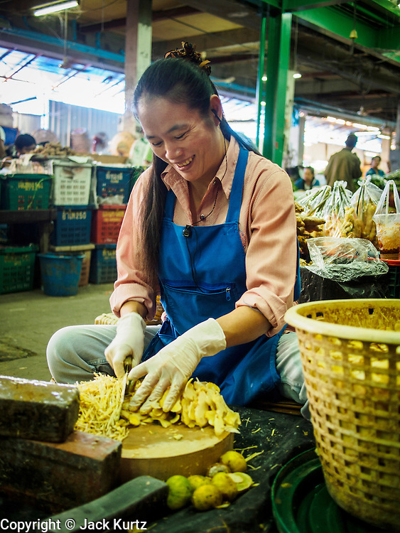 """19 DECEMBER 2013 - BANGKOK, THAILAND:    A vendor slices ginger in the flower market. Pak Khlong Talat (""""the market at the mouth of the canal"""") is a market in Bangkok that sells flowers, fruits, and vegetables. It is the primary flower market in Bangkok. It is located on Chak Phet Road and adjacent side-streets, close to Memorial Bridge. The market is open 24 hours, but is busiest before dawn, when boats and trucks arrive with flowers from nearby provinces.       PHOTO BY JACK KURTZ"""