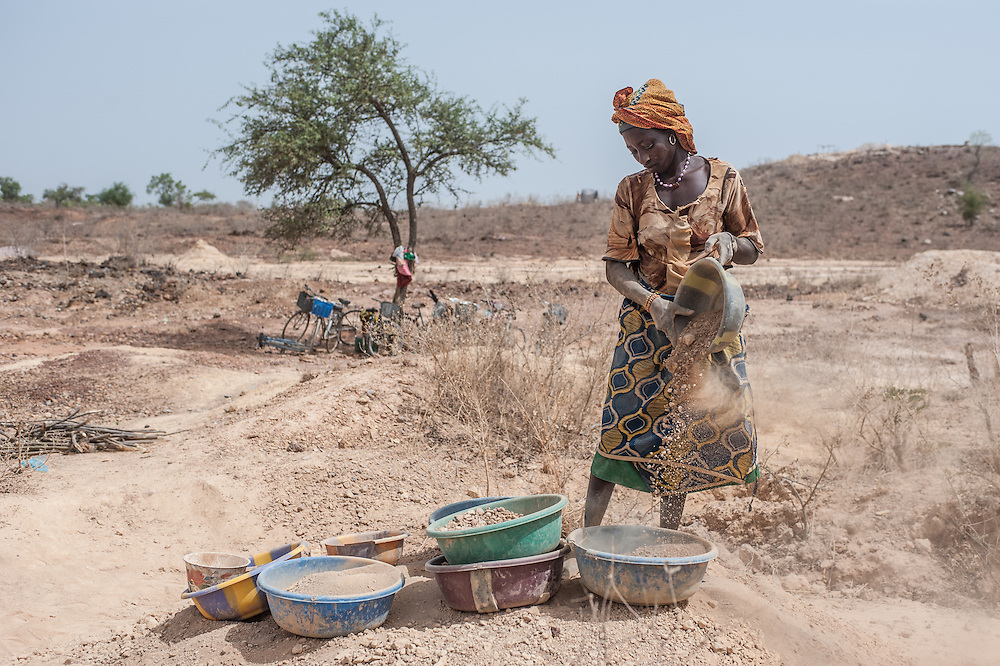 Nobsin, Burkina Faso - 13 May 2014: a woman sifts the ground in search for gold a few meters from the main gold vein