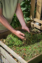 Adding soil to grass clippings on a compost heap to maintain balance and help them rot down.