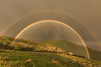 A weakening storm approached the west side of the Bighorn Mountains. The sun came out and this double rainbow appeared. It was so vivid it felt like I could reach out and touch it. At first it was almost a complete circle. I rushed to capture a time lapse and had to keep wiping the raindrops off my lens. I got quite wet as a result, but it was worth it.<br />