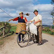 Portrait of Romanian peasant farmers returning from the fields with sacks of potatoes balanced on a bicycle in the Carpathian Mountains, Romania