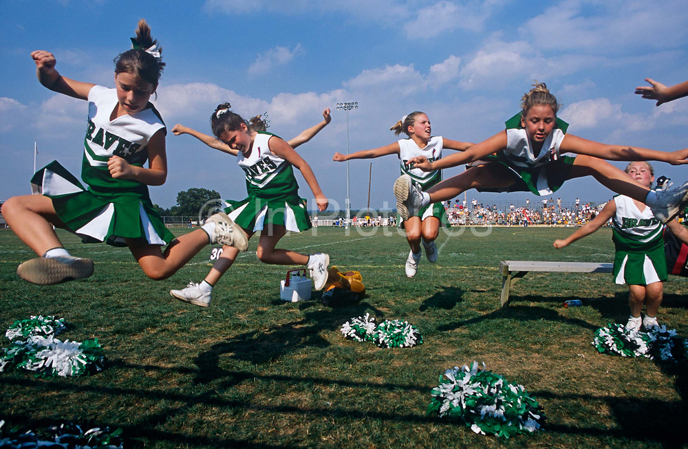 Leaping into the air all together are young members of the Donegal High School football cheerleaders squad in Mount Joy, Pennsylvania. On a Saturday afternoon as their team called the Braves take a break during their inter-school match, the young ladies wearing matching Irish-green colours leap in free manoeuvre on the instructions of their trainer. They have left their pom-poms on the grass and we see the rest of the sports-loving crowd in the bleachers on the far side of the pitch. Some choose to do mid-air leg splits, some a rather unelaborate twist and of some we only see arms merging with other bodies while others barely make it off the ground, such is their poor timing but there is generally lots of effort and energy in this brief spontaneous moment.